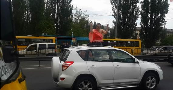 В столице Украины беременная девушка вылезла на крышу внедорожника, а затем бросалась под проезжающие автомобили 1