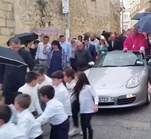 Десятки детей тащили по улице запряженный Porsche со священником